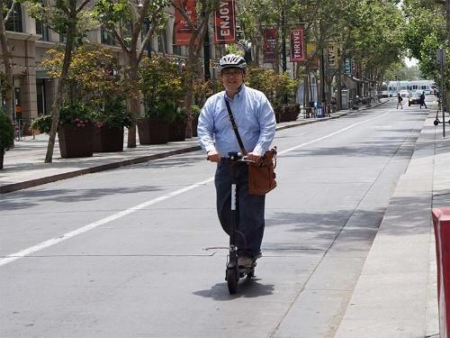 バードの電動スクーターに乗る記者。大人2人分の重量がある記者が乗ってもスムーズに走った