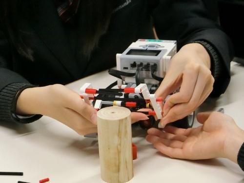 ロボットのアームの動きを検討しながらブロックを組む生徒たち