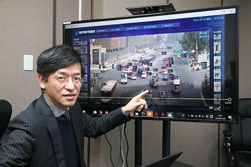 中国・西安の監視カメラ映像を示す、センスタイムジャパンの勞世竑(ラオ・シーホン)社長(写真:山田哲也)