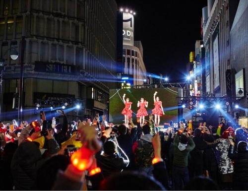 カウントダウン直前の渋谷のサテライト会場。この日のために設置した大型スクリーンに、横浜アリーナにいるPerfumeの生中継が映し出された。約2000人の観客には光る腕輪(PixMob)を配布し、横浜と渋谷で光を共有