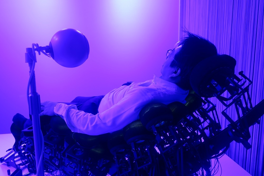 Media Ambition Tokyo 2019で、共感覚体験装置「Synesthesia X1-2.44」を体験する筆者。黒い椅子は44個の振動子をつなげて作っている。椅子の脇にある丸い装置はスピーカー