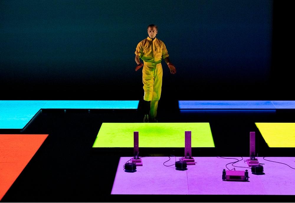 色が変わる床の上で踊るガルバン氏と機械。作業着のような黄色の服を着たガルバン氏は、フラメンコダンサーに見えない (出所:山口情報芸術センター)