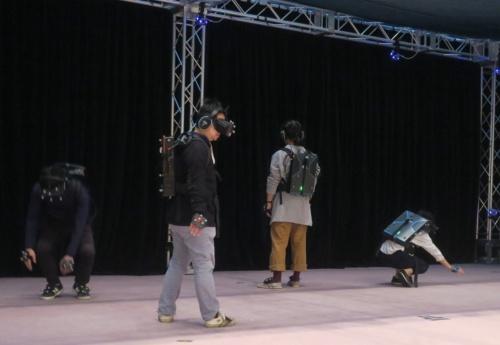 VRの体験中、5人は自由に動き回ってよい。立っている人(手前が筆者)、しゃがんでいる人などさまざま