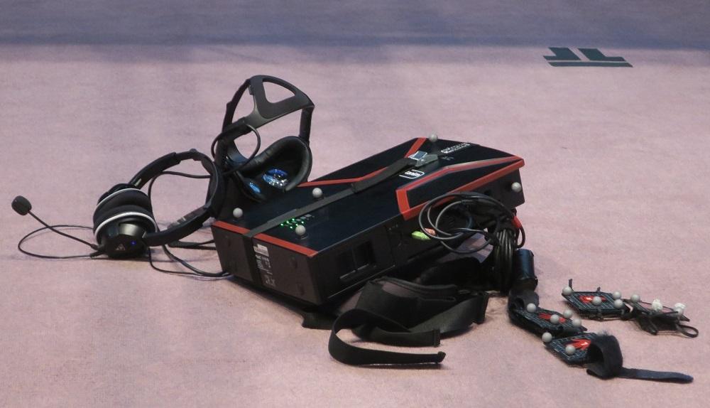 VR_Iを体験するため、参加者が装備する機器一式。VRを見るゴーグル、ヘッドホン、背負うパソコン、両手両足に着けるセンサーで構成されている