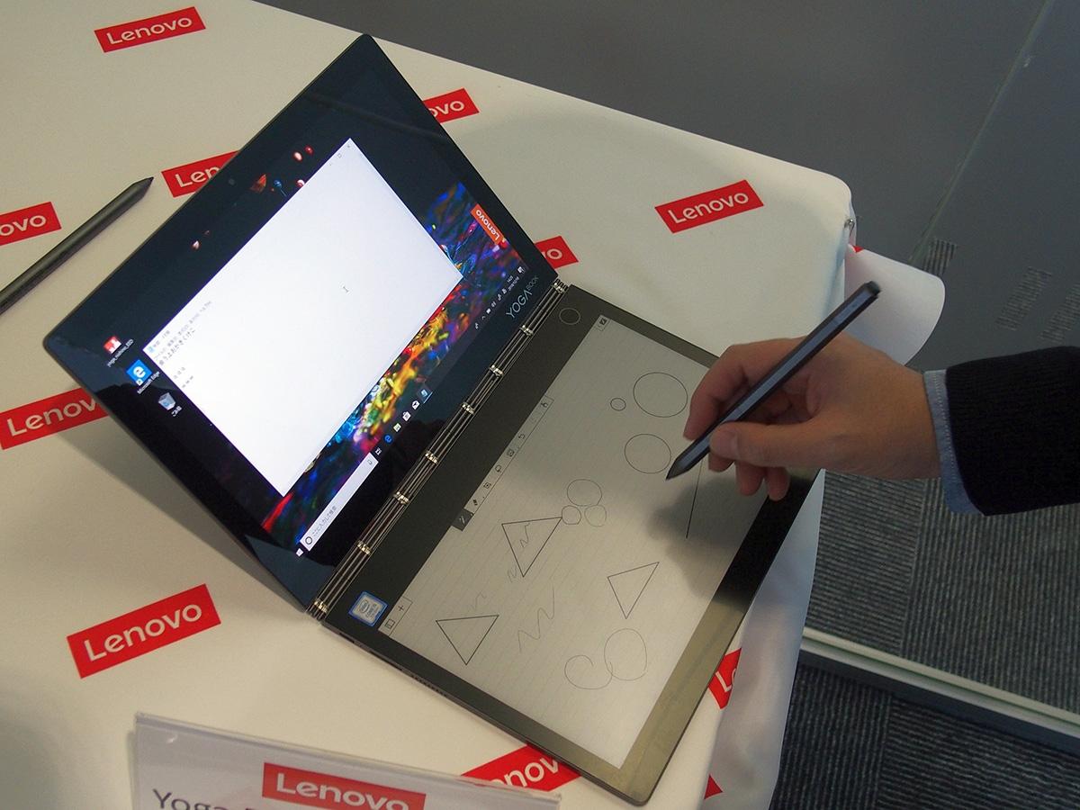 「Yoga Book C930」の外観。通常のノートPCならキーボードがあるところにE Inkによるディスプレーを搭載する。様々なレイアウトのキーボードを表示できるほか、写真のような手書き入力も可能だ (撮影:長浜 和也、以下同じ)