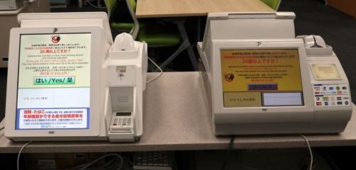 顧客側から見た新型レジ(左)と従来型レジの外観の違い。新型レジはディスプレーを12インチから15インチに大きくし、接触ICクレジットカード対応のピンパッドを付けた