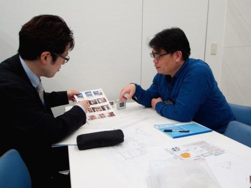 省エネ住宅の体験宿泊を総括する筆者(右)とYデスク(左)。測定した温度データと撮影した写真などをみながら、体験を振り返る(撮影:安井 功)