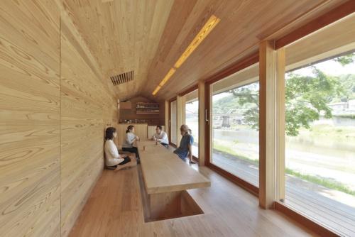 〔写真3〕川に向かって窓が並ぶ、開放的な1階のコミュニティースペース。床、天井、壁すべてを吉野産のスギで仕上げた。写真奥のキッチンカウンターに見える部分が、帳場スペース(撮影:生田 将人)