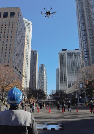 〔写真1〕新宿駅周辺防災対策協議会のメンバーによる実証実験。ドローンで取得した映像データから滞留者の人数などを分析し、遠隔地で対策を決定することなどを検証している(撮影:日経アーキテクチュア)
