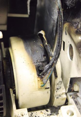 この住宅のファンモーター付近の状態。リード線接続部の焼け方が最も激しかった。火災の6カ月前にエアコンの内部を洗浄していた。(写真:福岡市消防局)