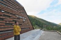 VUILDの秋吉浩気代表取締役。19年10月に富山県南砺(なんと)市利賀村に完成した「まれびとの家」の前にて