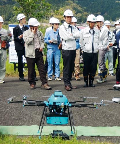 国土交通省が17年4月に京都府の由良川で実施した「陸上・水中レーザードローン」の現場実証の様子。パスコとアミューズワンセルフのグループが、陸上の地形を計測できるレーザードローンを持ち込んだ。建設コンサルタント会社などの技術者が100人ほど集まった(写真:日経コンストラクション)