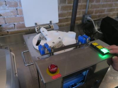 会場にスタンバイする試作機。3つの稼働パーツが動いて、三角形のおにぎりを作る。米のくっつきを防ぐため、稼働パーツはテフロン樹脂製にした