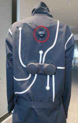 服の背中にある距離センサー(赤丸の部分)。服の模様に見える白い線には電子制御回路基板や振動子をつなぐ配線が通っている