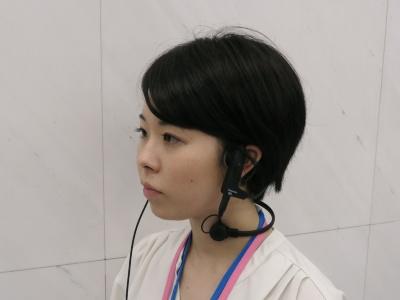 ヘッドセット本体「XC-CSH00G」にオプションのマイク「XC-CSH30G」を組み合わせて着用した様子。耳の前部分にイヤホンが、首の側面部分にマイクが密着した状態になる。マイクは首回りのネックリングで固定している