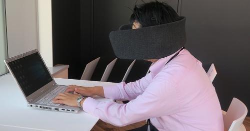 WEAR SPACEを頭に着けてパソコンに向かう筆者。パーティションで周囲は見えず、ヘッドホンのノイズキャンセリング機能で雑音もほとんど聴こえない