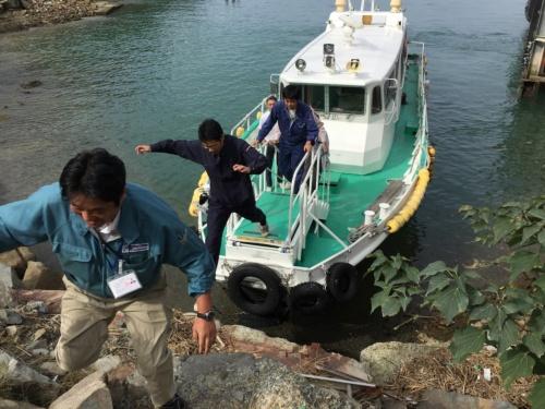 チャーター船で西島に上陸する水道の検針員たち