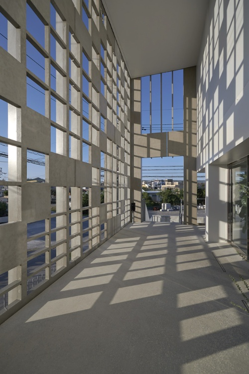 北西の外周を覆うHPCによるルーバーを2階の回廊から見る。沖縄固有のミンサー織りを抽象化した(写真:細矢 仁)