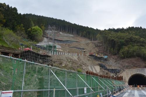 斜面崩壊部で復旧が進む。新しく架け直した立川橋から見上げた。2019年4月25日に現地を訪れた際は、斜面上部の水抜きボーリングが終わって、コンクリートが一部吹き付けられていた。斜面途中に見える複数の灰色のH形鋼が、流向制御工の一部(写真:日経コンストラクション)