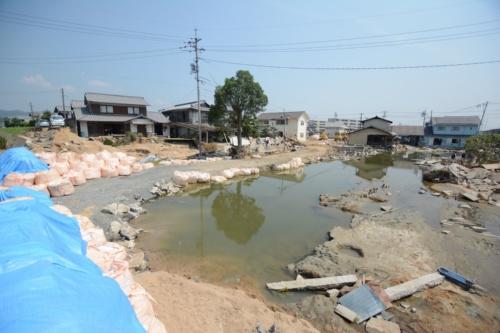 7月18日に撮影。豪雨から10日強たっても、まだ水が引いていなかった。破堤付近では全壊または、流失した住宅が多い。ただし、そこから少し離れると水には漬かっているものの、全壊は免れている住宅が見られた(写真:日経コンストラクション)