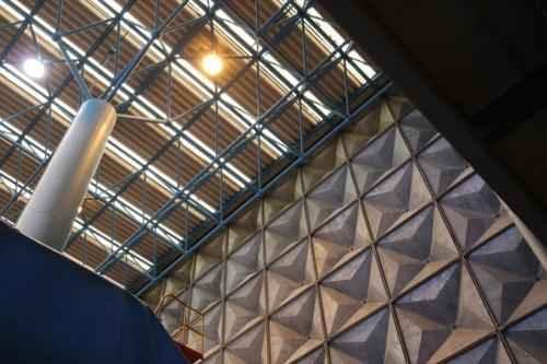 スペースフレームの屋根構造を6本の柱が支える(竣工時の柱は4本)。ストライプ状に設けられた天井のトップライトから自然光が入る。カーテンウオールはアルミ鋳物製パネル