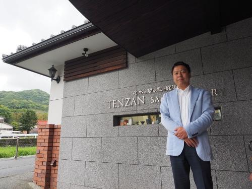 天山酒造本社前に立つ6代目社長の七田謙介氏