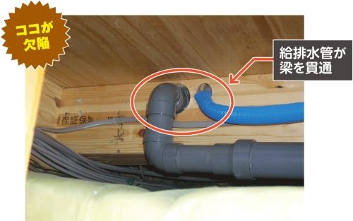 〔写真1〕2階の床下にある梁に、排水管と給水管がそれぞれ梁を貫いて設置されていた。梁の中央部ではないものの、構造材に当たるので安全性に配慮して補強した(写真:カノム)