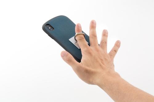 スマホリングはスマホ本体やケースの背面に取り付けて使う。リングに指を通して持てば、手が滑ってもスマホの落下を防ぎやすい