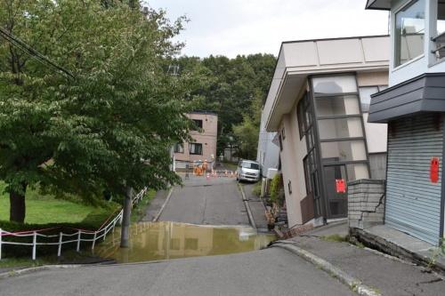 公園の脇の道で大きく傾いた住宅。赤い紙は、市の応急危険度判定で「危険」な状況と判定されたことを示す。水道管が被害を受けたのか、汚水がたまっていた(写真:日経コンストラクション)