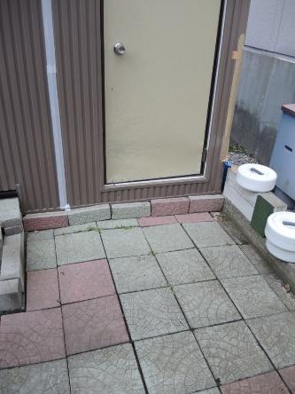 公園の東側にある近藤氏の敷地では、地震後に地面に張ったタイルが凸凹になった。目地の隙間も広がっている。地盤が陥没して住宅が全壊した隣の敷地側に、住宅や土留めが傾いた(写真:日経ホームビルダー)