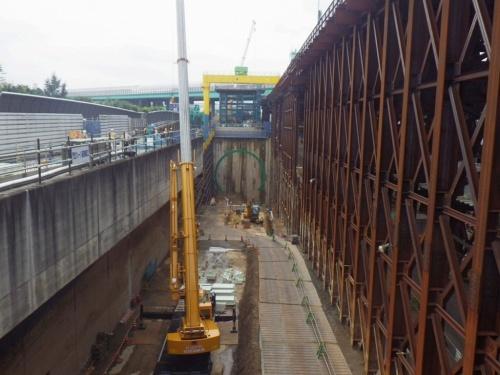 本線トンネル(南行)大泉工事のたて坑。すぐ左に東京外かく環状道路が通る。たて坑には機材を置くほか、大型のトラックが通るスペースも確保しなければならない。右側に見える巨大な仮設の奥には、同じような空間が広がり、そこでは大成建設・安藤ハザマ・五洋建設・飛島建設・大豊建設JVが「本線トンネル(北行)大泉南工事」のシールド機を組み立てる(写真:東京外環プロジェクト)
