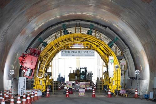 模擬トンネル内に据え付けたマシン。左側の赤い部品がエレクターの腕で、背後に見える緑の部品が形状保持装置の腕(写真:清水建設)