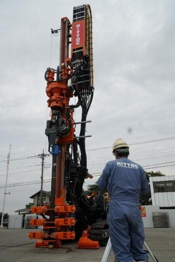 日特建設などが開発したハイグランツドリル。2020年11月に埼玉県久喜市の中央機材センターで公開した。高さは8mで、輸送時は折りたたむ。手前は操縦者(写真:日経クロステック)