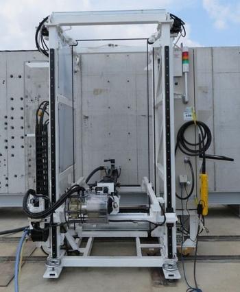 大径用の自動削孔マシン。空圧削岩機や集じん機、制御盤などを搭載。クレーンで吊り上げるなどして現場に搬入する(写真:奥村組)