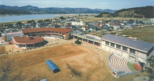 裏山の高台から眺めた大川小学校の遺構。鉄筋コンクリート造の2階建ての校舎だった。被害の様子から津波が2階の高さまで到達していたことが分かる。石巻市は震災体験の伝承や防災教育に役立てるため保存する方針を表明している(写真:北澤建築設計事務所)