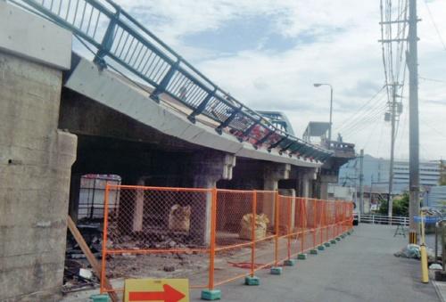 南側の側面から見た事故発生当時の御館橋。歩道が垂れ下がり、柵だけで何とか落下を食い止めているように見える (写真:福岡県)