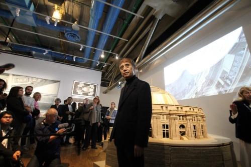 内覧会でパリの人たちの質問に答える安藤氏。後ろの模型は、ポンピドー・センター近くで現在、改修工事中のブース・デ・コマース(写真:日経アーキテクチュア)
