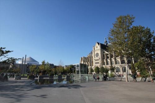 ネルソン・マンデラ公園の東側からブース・デ・コマースを見る(左奥)。仮囲いですっぽり覆われているため、市民もかなり気になっているようだ。右に見えるのは、パリで最も美しい外装の教会ともいわれるサン・トゥスタッシュ教会(写真:日経アーキテクチュア)