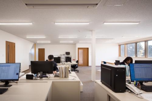 2階事務所。1階同様、4550mmグリッドに150mm角の柱を配置しているため所々に柱が見える(写真:浅田 美浩)