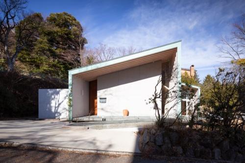南側外観。左側の木製建具が玄関ドア。前面道路との間はスロープで行き来する。東から西に向けて下る片流れの屋根形状は、建物内部ではそのまま天井面の形状になっている(写真:浅田 美治)