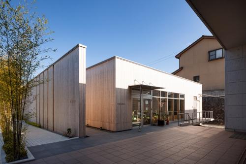 茶室「早瀬庵」へのアプローチ。高くそびえるLVL製の塀と、右手の手焼き体験施設との間に生み出された露地を進むと、茶室の出入り口が現れる(写真:浅田 美浩)