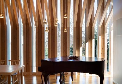 Casa di Enの内観。縦長スリット状の開口部から日差しを取り込む。この柱のように目立つ箇所の構造材には、一般流通材である105mm角のヒノキ製材を用いている(写真:浅田 美治)