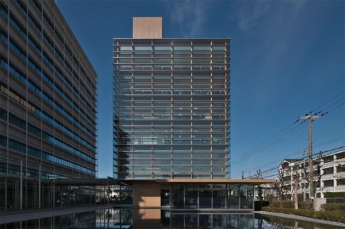 東から見たタクマビル新館の外観。建物は地上6階建て。2階から6階までの全面を覆うガラスのダブルスキンを、集成材だけで支持している。集成材はすべて現しで使った。建物は、木造と鉄骨造の混構造で、基礎免震を採用している。左に見えるのは、既存の本館(写真:生田 将人)