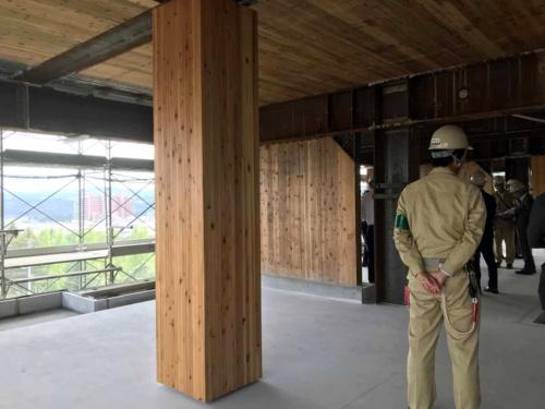 手前は燃エンウッドの柱。完成後もそのまま住戸内で木部が見える。奥に見えるのがCLT耐震壁。完成後はCLT耐震壁、CLT床・天井ともに耐火被覆で覆われて木部は見えなくなる(写真:村島 正彦)