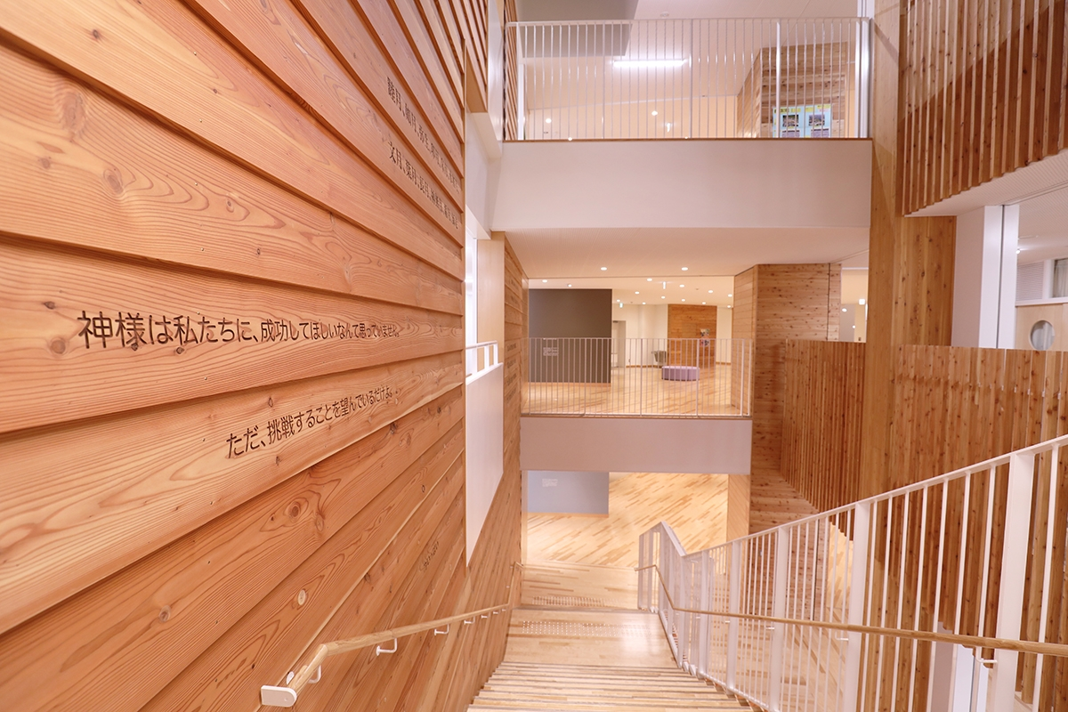 廊下・階段を含む共用部の「木の回廊」は木質化し、階段部は3層にわたって吹き抜けとした。階段脇の下見板張りの壁には世界のことわざや格言などを彫り込んだ(写真:都築 雅人)