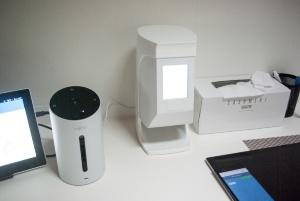机の上には各種デバイスや、操作のためのスマホ・タブレットなどがある。写真中央にあるのが、資生堂(東京・中央区)の美容デバイス「Optune(オプチューン)」。その左にあるのが富士通コネクテッドテクノロジーズ(川崎市)の「健康をアドバイスするエージェントデバイス」(写真:村田皓)