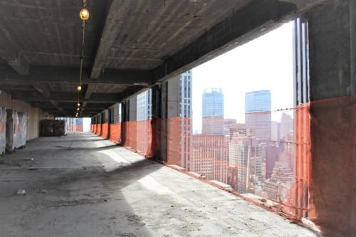 大規模改修工事中の1271アベニュー・オブ・ザ・アメリカスの38階。ビル外装のコンクリートを取り払って、新しい窓枠を取り付ける工事が進んでいる。ぽっかりと空いた壁面からマンハッタンを代表する名建築「メットライフビル(旧パンナムビル)」が見える(写真:日経アーキテクチュア)