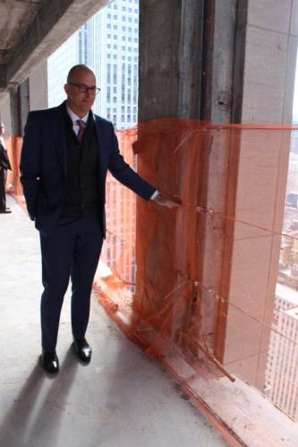 改修前の腰壁の高さ示すロックフェラーグループ社のビル・エドワーズ・シニアバイスプレジデント。窓面は従来比で約6割拡大した(写真:日経アーキテクチュア)