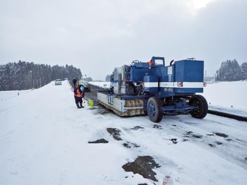 除雪作業の様子。路上表層再生工法などに使う建機のヒーターで加熱する(写真:日本道路)