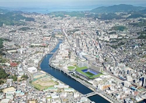 長崎スタジアムシティの全体イメージ(合成画像中、浦上川の右岸)と市街地の様子。長崎市は、都市計画マスタープランに「ネットワーク型コンパクトシティ長崎」を位置づけ、立地適正化計画を策定。工場跡地である同プロジェクトの敷地に関しては、商業・業務地に転換を図る方向で都市計画の見直しを進めている。以下、デザインなどは今後変更の可能性がある(資料:ジャパネットホールディングス)